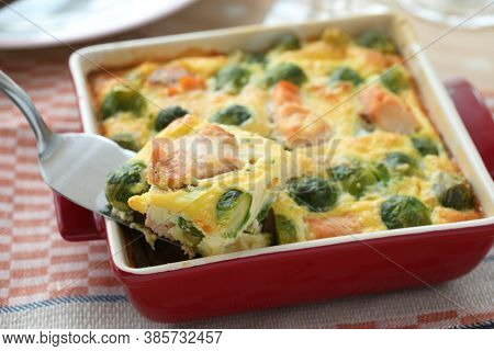 Salmon and Brussels sprout gratin in a red baking dish closeup. Selected focus on the piece on a cake server