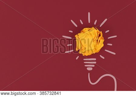 Idea Concept With Lightbulb Made Out Of Yellow Crumbled Paper Ball And Drawn White Lines On Dark Red