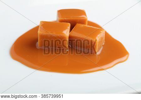 Three blocks of fudge under caramel sauce on white background