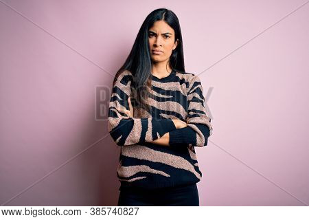 Young beautiful hispanic woman wearing animal print sweater over pink background skeptic and nervous, disapproving expression on face with crossed arms. Negative person.