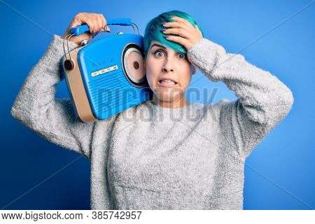 Young woman with blue fashion hair listening to music holding vintage portable radio stressed with hand on head, shocked with shame and surprise face, angry and frustrated. Fear and upset for mistake.