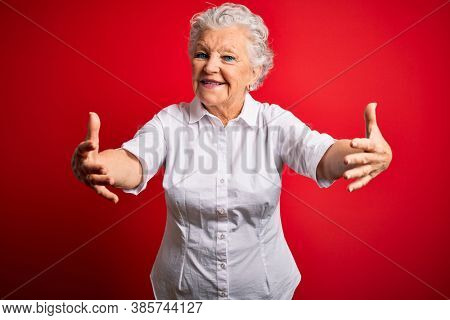 Senior beautiful woman wearing elegant shirt standing over isolated red background looking at the camera smiling with open arms for hug. Cheerful expression embracing happiness.