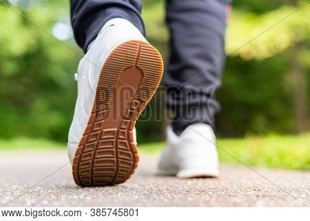 Runner Feet Running On Road Closeup On Shoes. Man Fitness Sunrise Jogging Workout Welness Concept.