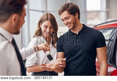 Cheerful Young Man And Woman Receiving Keys Of New Automobile From Professional Dealer In Car Salon