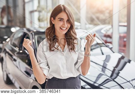 Delighted Young Female Clenching Fists And Smiling For Camera While Buying New Car In Dealership