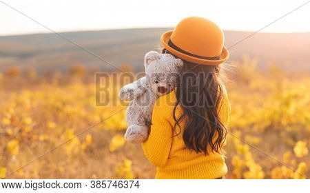 Back View Of Unrecognizable Sad Little Girl In Yellow Sweater And Hat Cuddling Teddy Bear While Stan