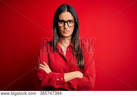 Young beautiful brunette woman wearing casual shirt and glasses over red background skeptic and nervous, disapproving expression on face with crossed arms. Negative person.