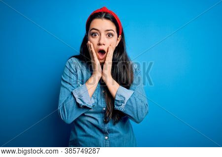Young brunette woman wearing casual denim shirt over blue isolated background afraid and shocked, surprise and amazed expression with hands on face