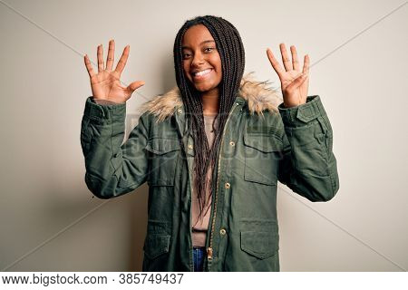 Young african american woman wearing winter parka coat over isolated background showing and pointing up with fingers number nine while smiling confident and happy.