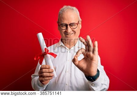 Middle age hoary student man wearing glasses holding university graduated degree diploma doing ok sign with fingers, excellent symbol