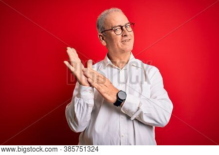 Middle age handsome hoary man wearing casual shirt and glasses over red background clapping and applauding happy and joyful, smiling proud hands together