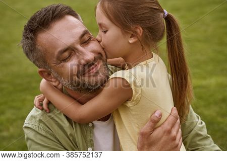 Fathers Day. Cute Little Girl Hugging And Kissing Her Happy Dad While Sitting On A Green Grass