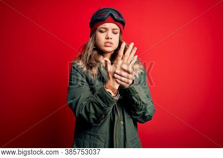Young blonde girl wearing ski glasses and winter coat for ski weather over red background Suffering pain on hands and fingers, arthritis inflammation