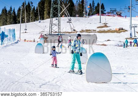 Young Happy Skier Girl Learning How To Ski With Her Mom On The Green Ski Zone, Bialka Tatrzanska, Ta