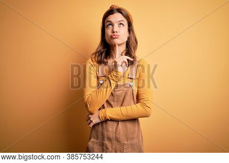 Young beautiful blonde girl wearing overall standing over yellow isolated background Thinking concentrated about doubt with finger on chin and looking up wondering