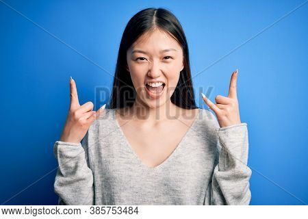 Young beautiful asian woman wearing casual sweater standing over blue isolated background shouting with crazy expression doing rock symbol with hands up. Music star. Heavy music concept.