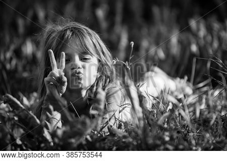 Little girl laying in grass. Black and white photo.