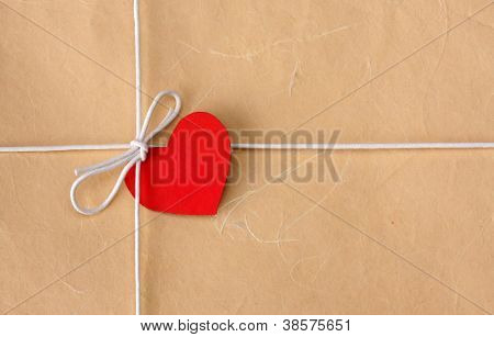 A bow from a string with valentine card on a brown packing paper