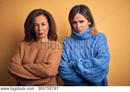 Middle age beautiful couple of sisters wearing casual sweater over isolated yellow background skeptic and nervous, disapproving expression on face with crossed arms. Negative person.