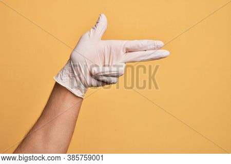 Hand of caucasian young man with medical glove over isolated yellow background gesturing fire gun weapon with fingers, aiming shoot symbol