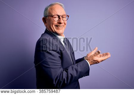 Grey haired senior business man wearing glasses and elegant suit and tie over purple background pointing aside with hands open palms showing copy space, presenting advertisement smiling excited happy