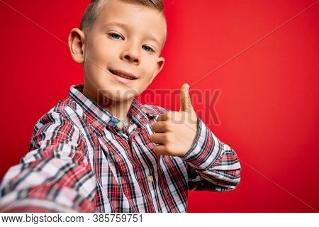 Close up of young little caucasian kid with blue eyes taking a selfie photo over red background happy with big smile doing ok sign, thumb up with fingers, excellent sign
