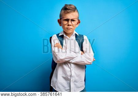 Young little caucasian student kid wearing smart glasses and school bag over blue background skeptic and nervous, disapproving expression on face with crossed arms. Negative person.