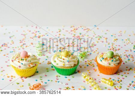Three Brightly Colored Homemade Cupcakes On A White Wooden Background With Sprinkles. Festive Birthd
