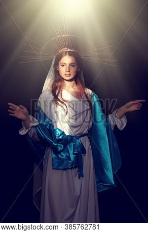 The Virgin Mary portrait on a dark background with rays of light. Modern art in religion.