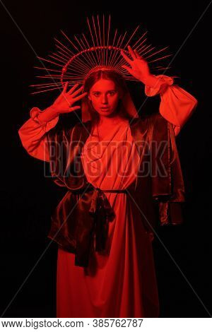 The Virgin Mary portrait in red light on a black background. Modern art in religion.