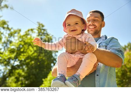 family, fatherhood and people concept - happy father with baby daughter at summer park