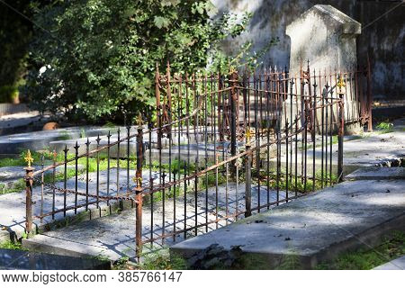 Tombstones And Old Rusty Fences On A Cemetery In Rotterdam In The Netherlands