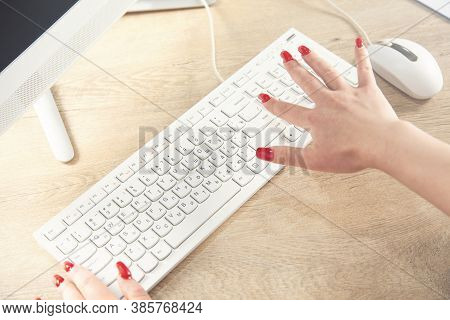 Sideview Of Female Hands Using Computer On Table With Glasses And Other Stuff