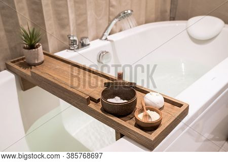 Modern And Comfortable Bathroom, Bath Tub With Wooden Table And Toiletries, Salt, Herb, Bath Bomb.
