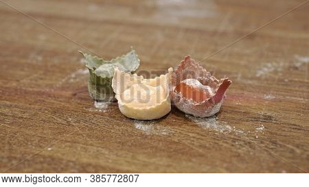 Three Raw Uncooked Italian Green, White And Red Ravioli On Wooden Table, Italian Flag Colour. Close