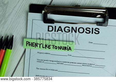 Diagnosis And Phenylketonuria Write On A Paperwork Isolated On Wooden Table.