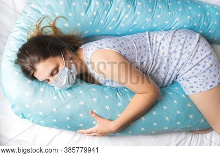 Pregnant Woman Sleeps In Nightgown, Medical Face Mask In Bed On Blue Comfortable Supporting Pillow W