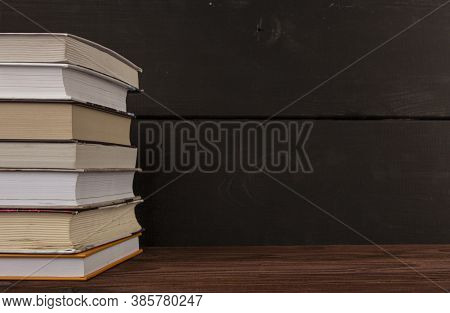 Close-up Stack Of Books On A Wooden Table With Space For Text. Books In The Library On The Table. Li