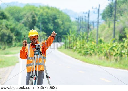 Engineer Working With Theodolite Transit Equipment And Command Radio Communication At Road Construct