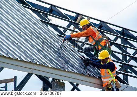 Construction Worker Install New Roof At Construction Site,electric Drill Used On New Roofs With Meta