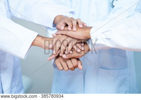 Portrait Of Medical Team Piling Hands Together In A Symbol Of Unity.