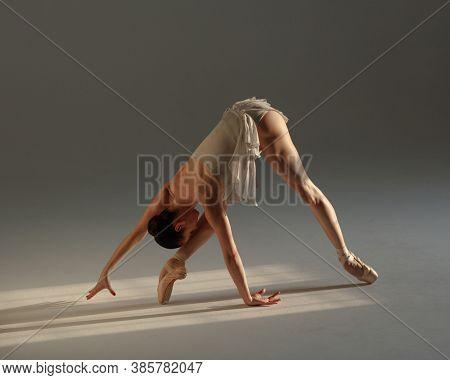 Young beautiful ballet dancer is posing in studio