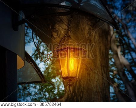 Retro Style Lantern Shines With Warm Yellow Light At Dusk. Vintage Lantern Hangs On A Chain Under Th