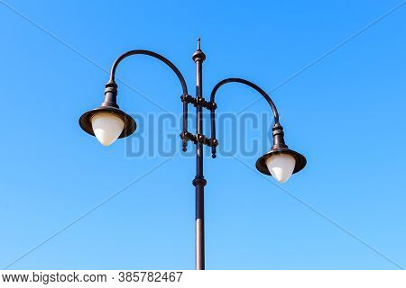Street Lamp With Two Bulbs Against A Blue Sky On A Sunny Day. Vintage Style Double Lamp Post Outdoor