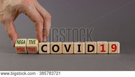 Test Result Of A Corona Test. Male Hand Turns A Cube And Changes The Expression 'positive Covid19' T