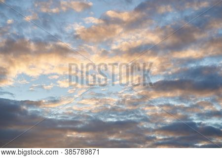Beautiful Evening Blue Sky At Sunset With Flaming Bright Light Clouds. A Warm Summer Evening At Suns