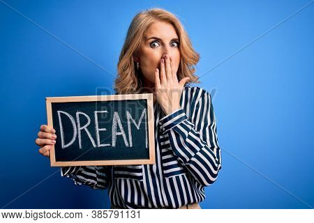 Middle age beautiful blonde dreamer woman holding blackboard with dream message cover mouth with hand shocked with shame for mistake, expression of fear, scared in silence, secret concept