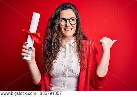 Young beautiful woman with curly hair holding university diploma degree over red background pointing and showing with thumb up to the side with happy face smiling