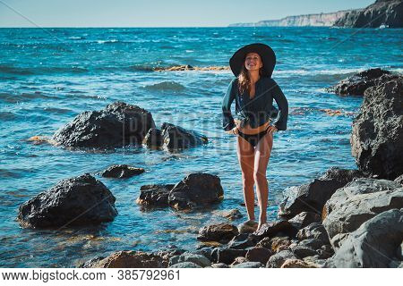 Smiling And Happy Woman In Hat. Rocky Coastline And Blue Sea. Meditation And Moment Of Relaxation. S