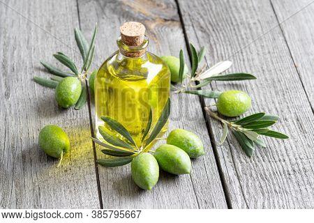 Green natural olives with bottle of olive oil on a vintage old wooden table.